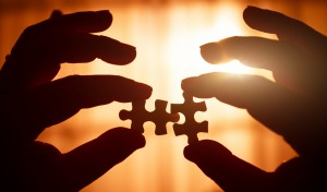 Two hands holding puzzle pieces conveying partnership solutions