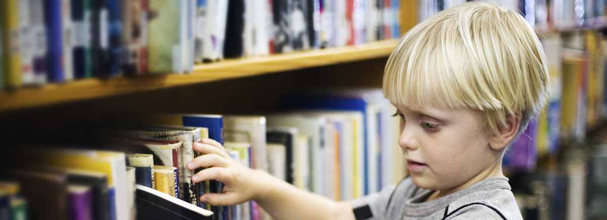 Boy looking at library books