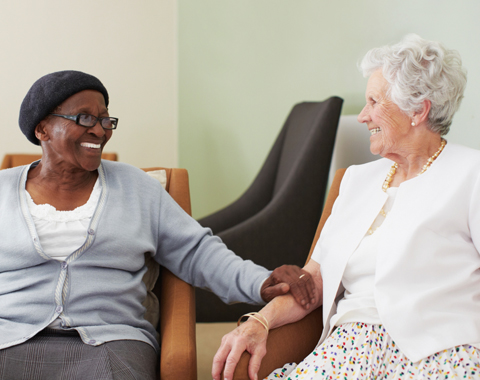Two female older adults chatting in a seniors' residence