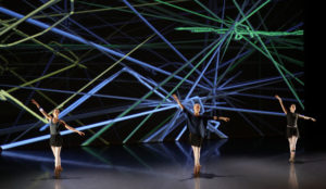 image of 3 ballerinas on stage dancing with laser light show behind them