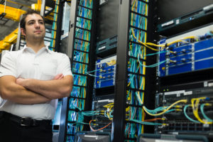 A happy datacenter manager posing in front of the datacenter equipment racks.