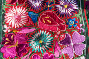 image of tapestry in red, purple, green and other colours, embroidered flowers