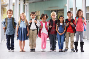 8 kids of various ethnicity and genders lined in a row smiling