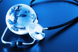 image in blue tones and silver, of small globe and stethoscope laying beside it